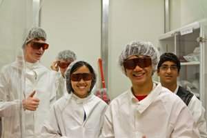 Summer Institute students smiling while wearing safety chemical suits